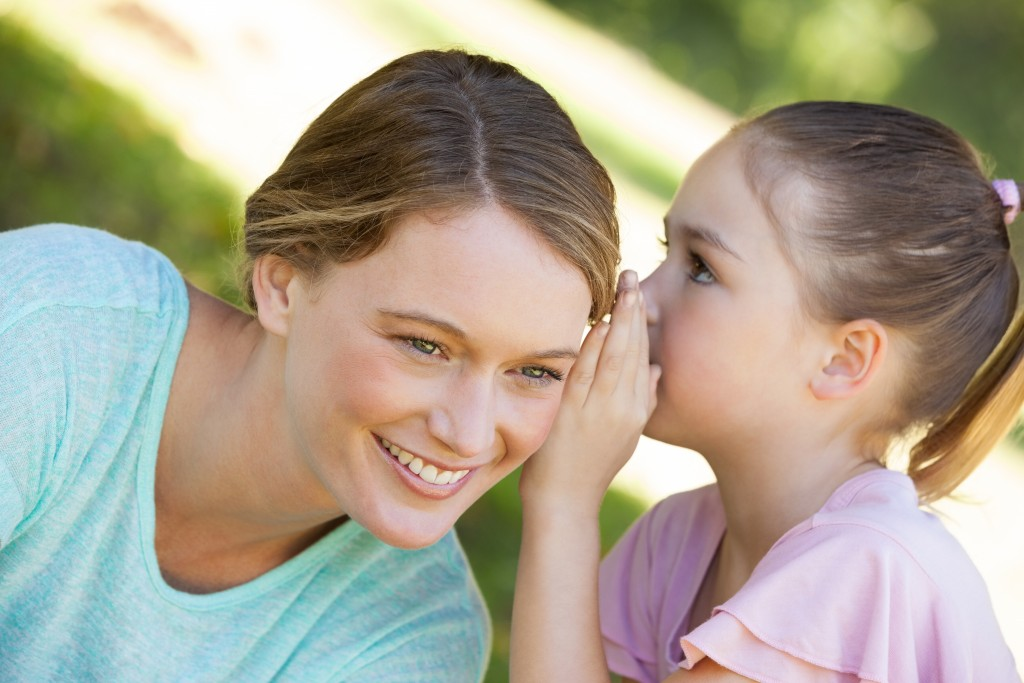 Close-up of a little young girl whispering secret into mother's ear at the park