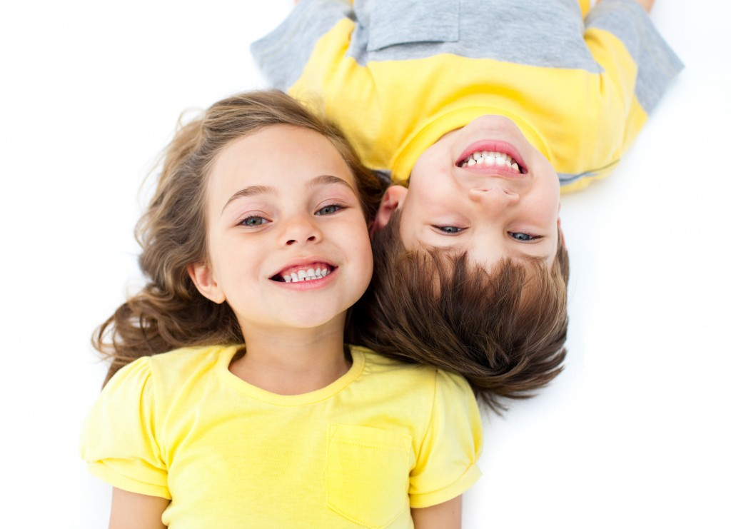 Smiling siblings lying on the floor against a white background