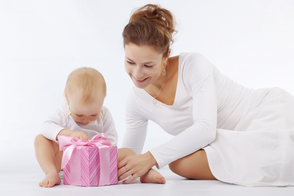 Portrait of mother with her baby opening gift box in white studio
