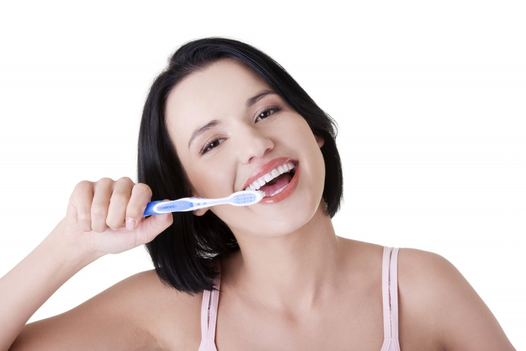 Woman with great teeth holding tooth-brush, isolated