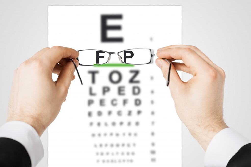 medicine and vision concept - man looking at eye chart through eyeglasses