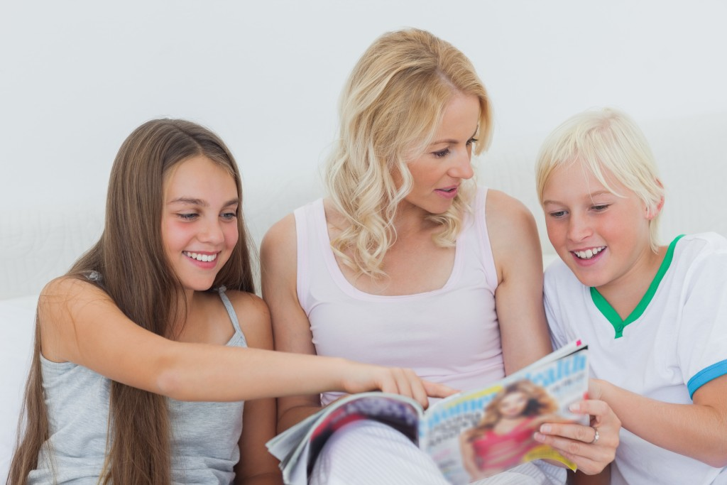 Girl pointing at a magazine in her mother hands next to her brother