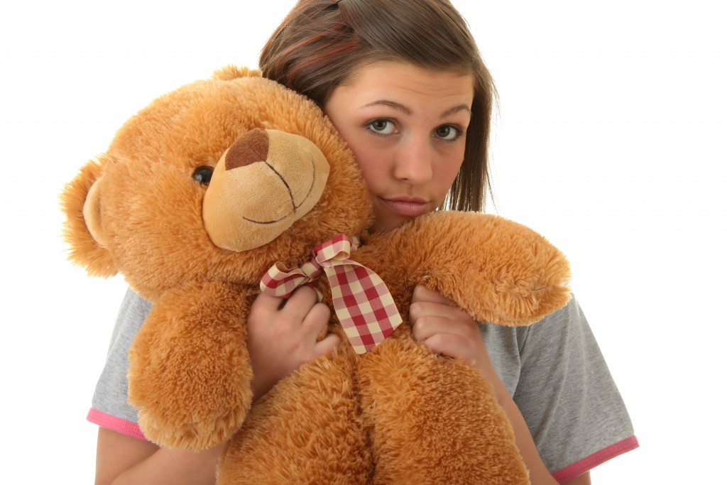 Beautiful teenager holding a teddy bear - isolated on white background