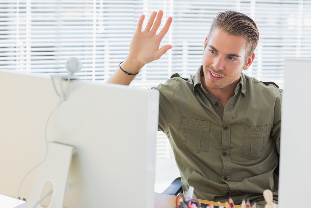Creative business employee waving during a videocall