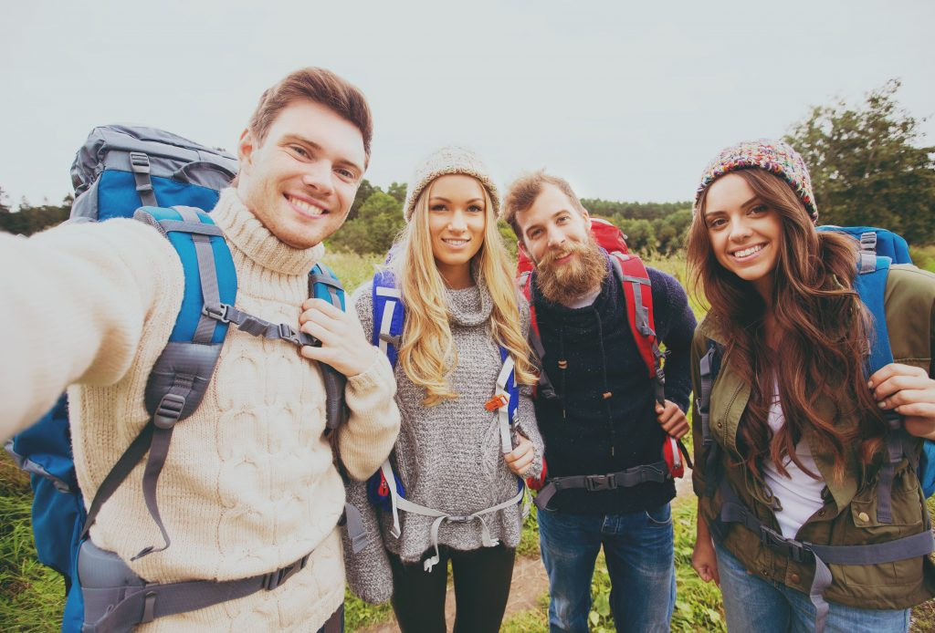 adventure, travel, tourism, hike and people concept - group of smiling friends with backpacks making selfie outdoors