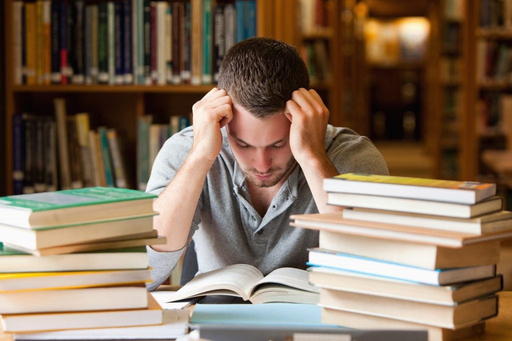 Tired student having a lot to read in a library