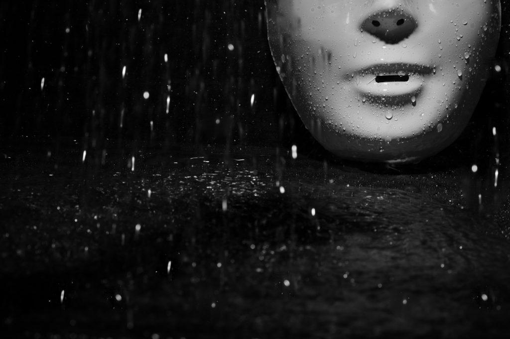 Plastic mask under the rain on a dark background