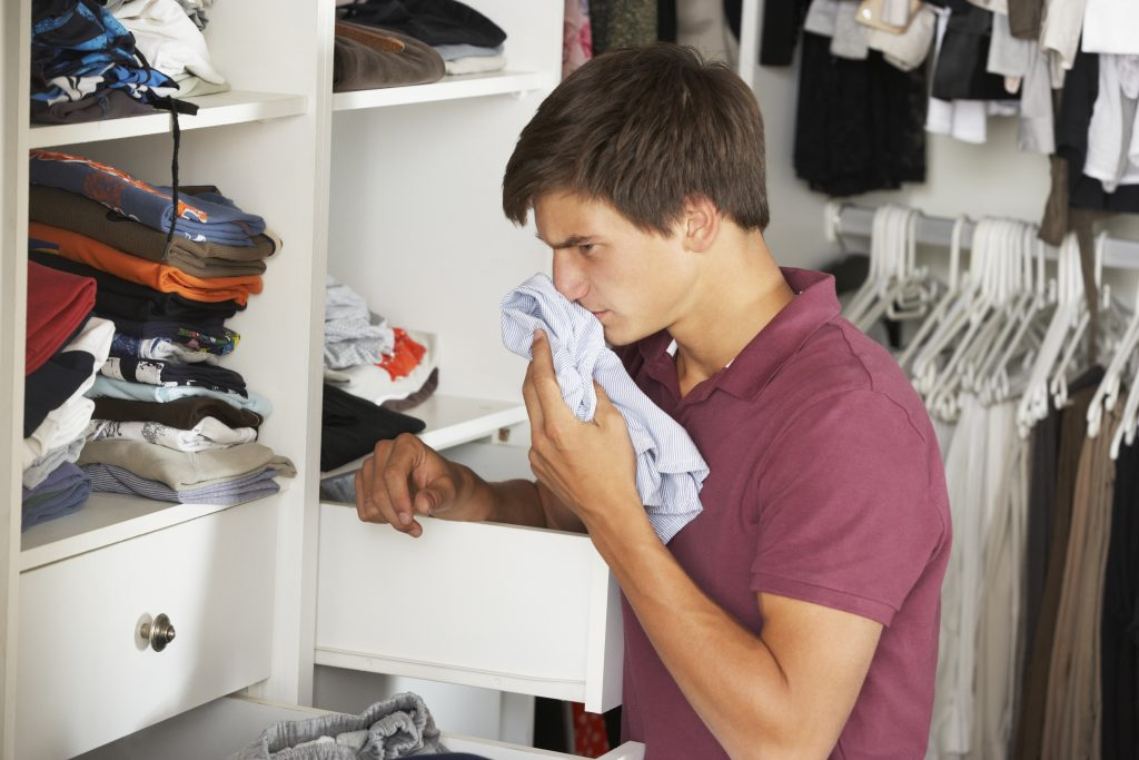 Teenage Boy Checking Freshness Of Clothes In Wardrobe