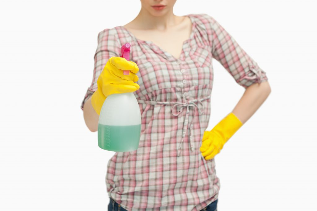 Close up of a woman holding a spray bottle against white background