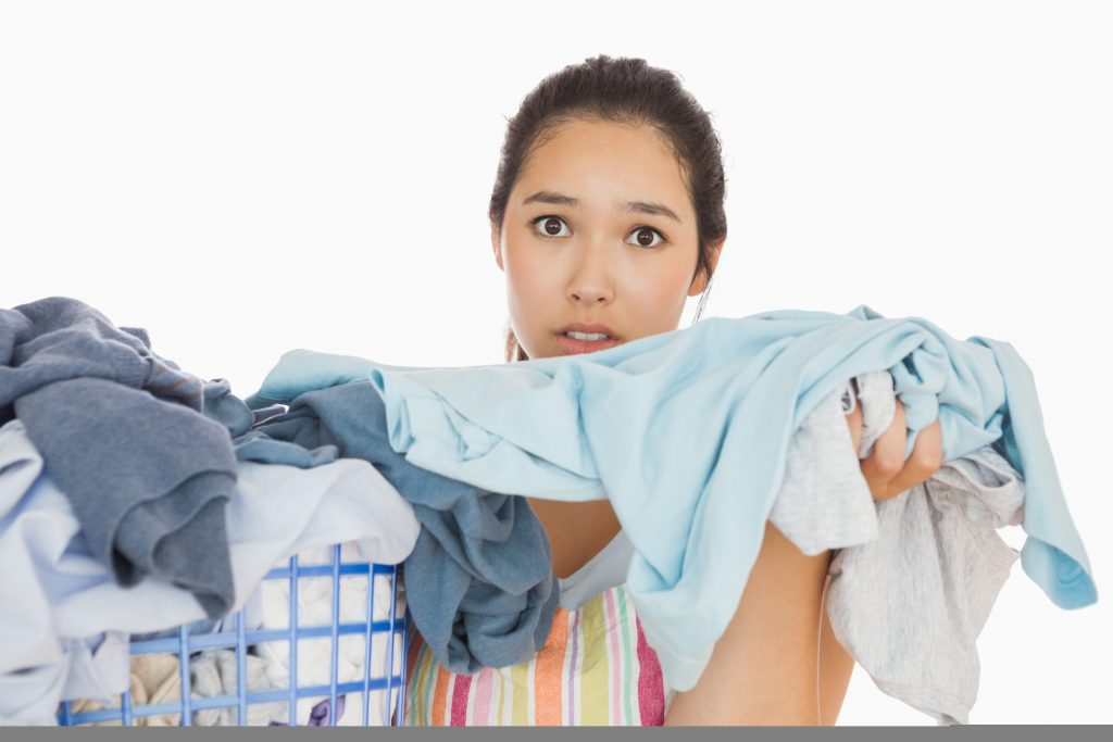 Frowning young woman taking out the dirty laundry from the basket