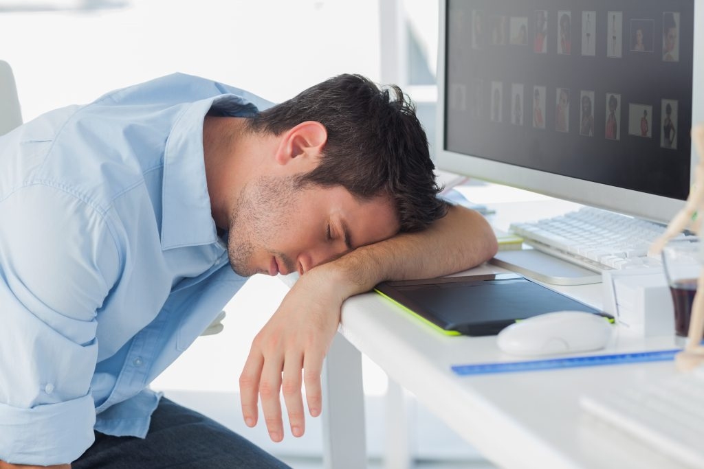 Graphic designer sleeping on the keyboard in his office