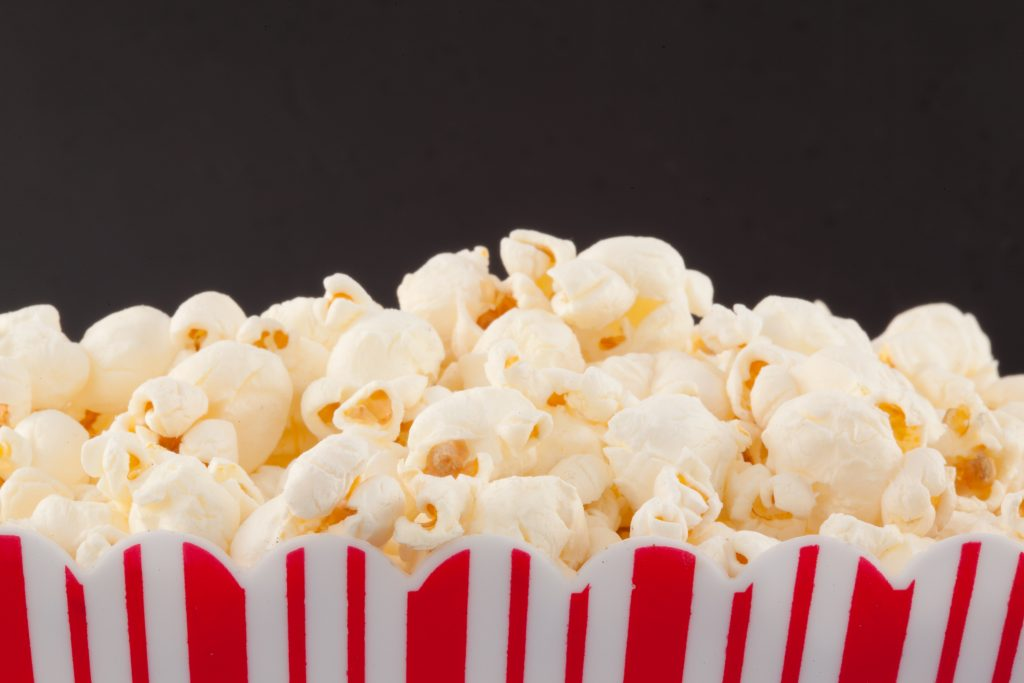 Close up of a top of a box full of pop corn against a black background