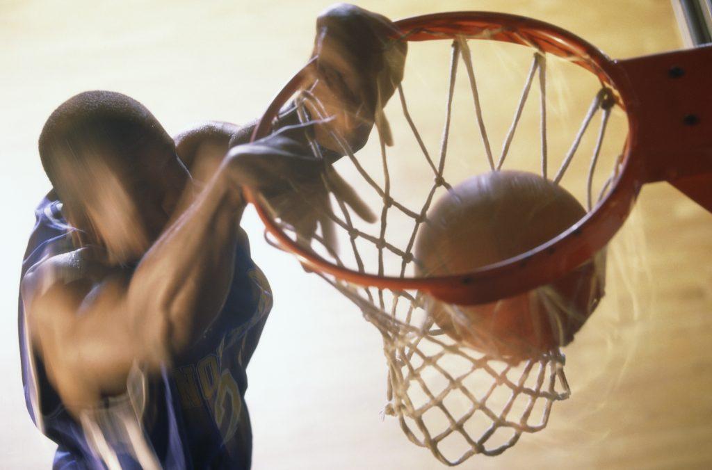 Basketball player slam dunking a ball
