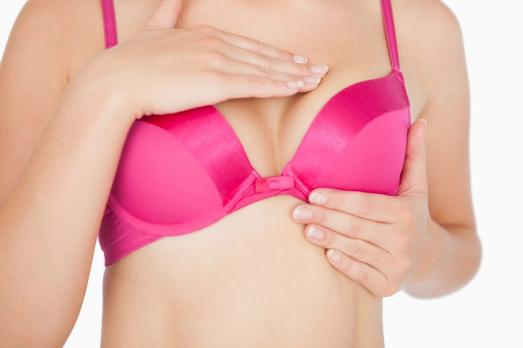 Close-up of woman performing self breast examination over white background