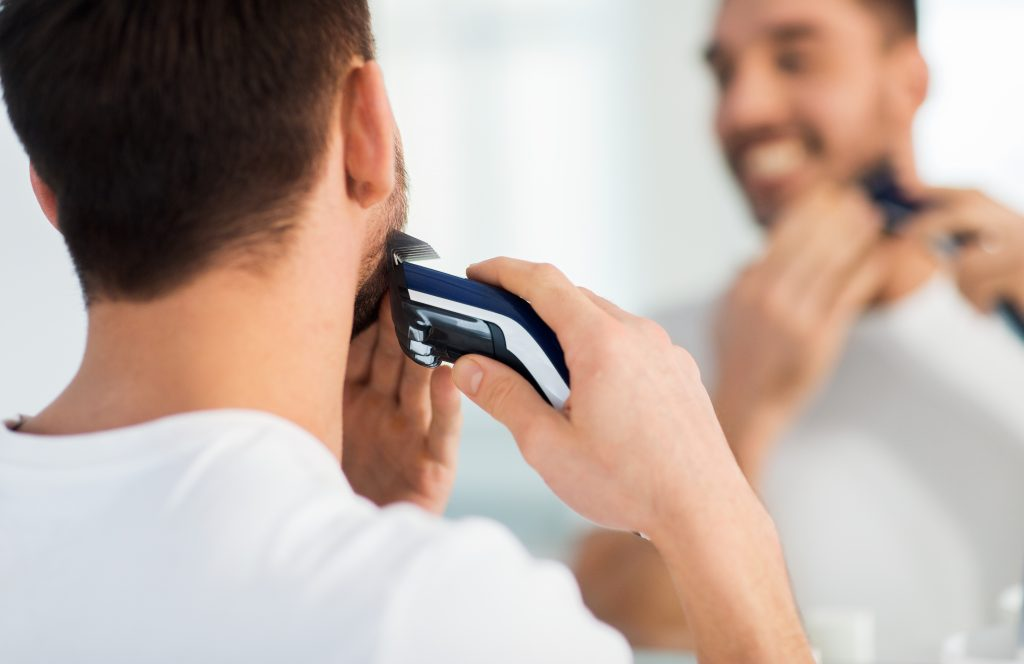 beauty, shaving, grooming and people concept - close up of young man looking to mirror and shaving beard with trimmer or electric shaver at home bathroom