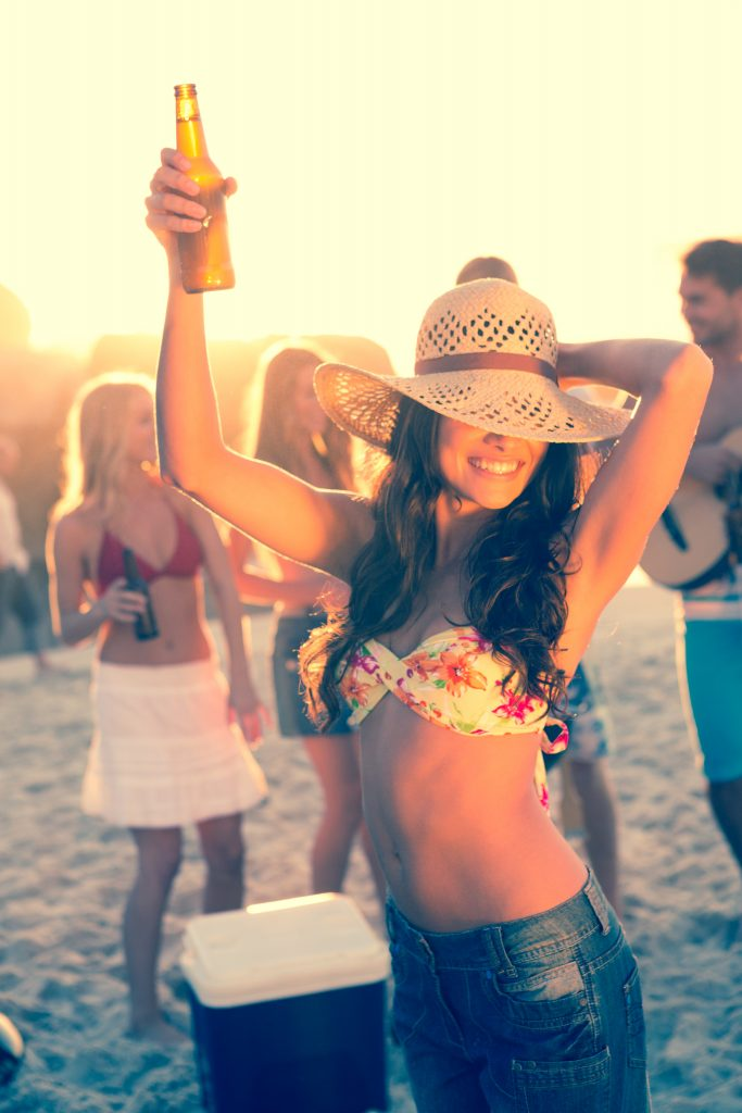 Woman holding beer during a party with her friends on the beach