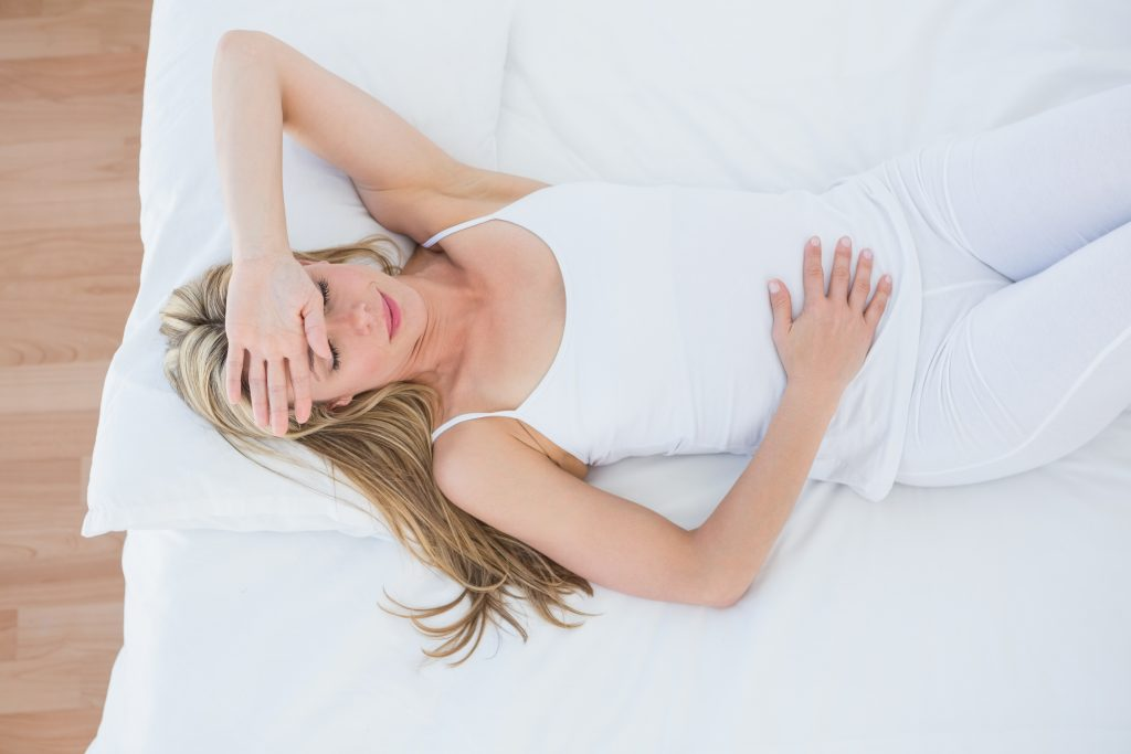 Blonde woman lying suffering from stomach pain at home in the bedroom