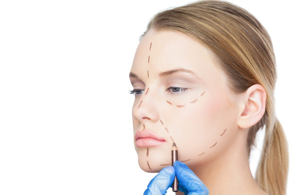 Surgeon drawing dotted lines on pretty patient before surgery