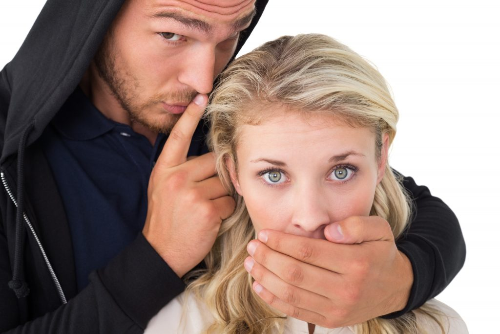 Close up of theft covering young womans mouth over white background
