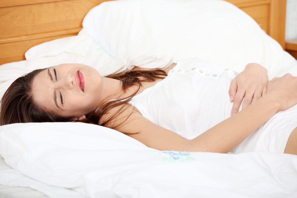 Young woman stroking her belly becouse of bellyache