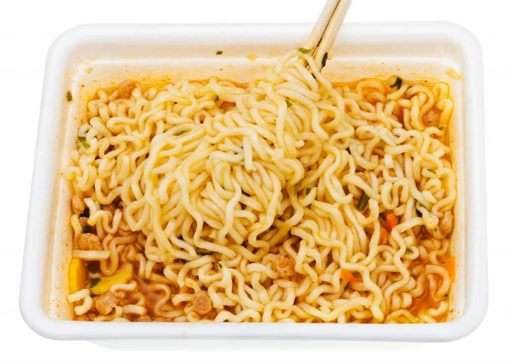 eating of instant noodles by wooden chopsticks from lunch box isolated on white background