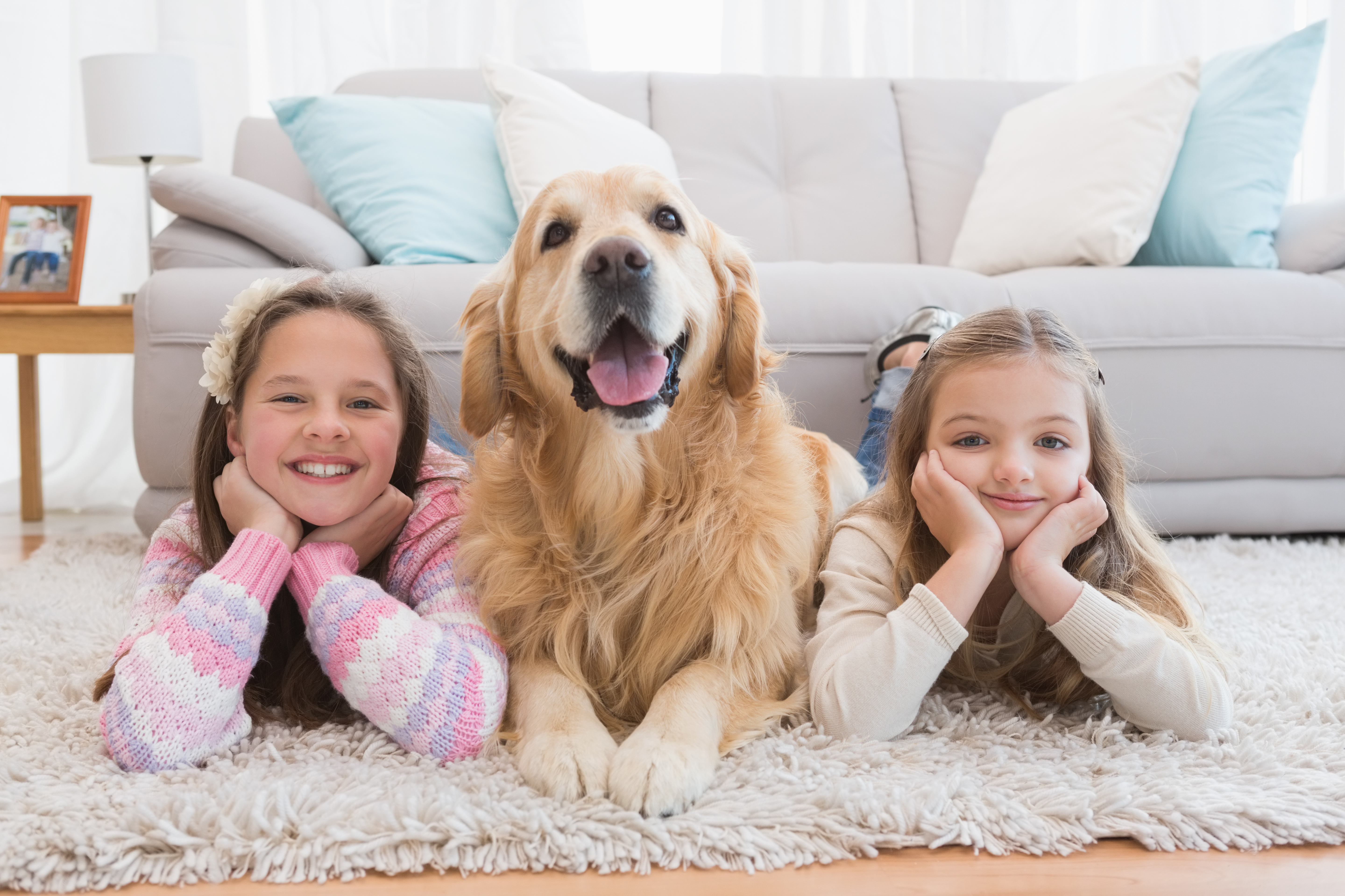 Sisters lying on rug with golden retriever smiling at camera at home in the living room
