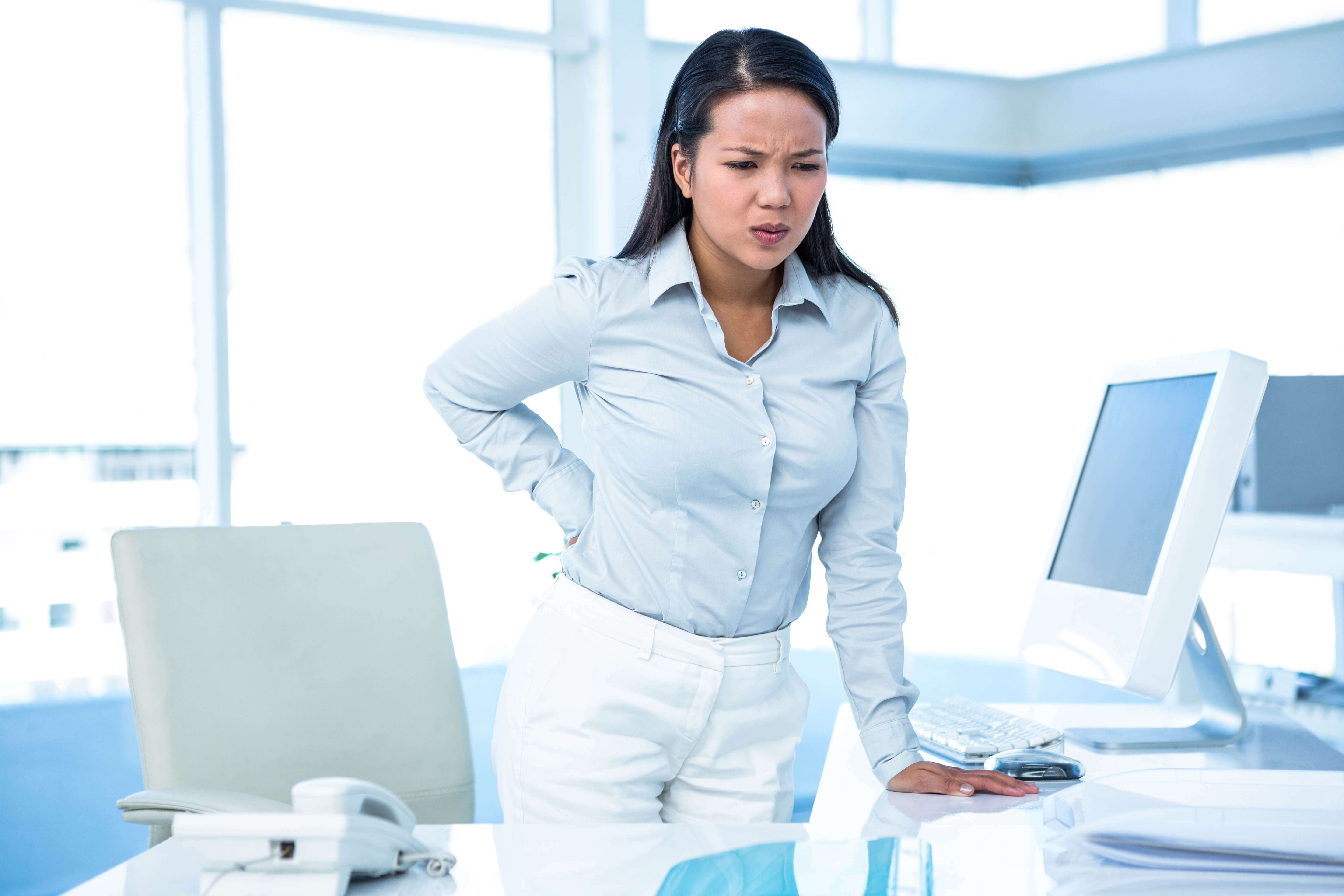 Frowning businesswoman with back ache standing in office
