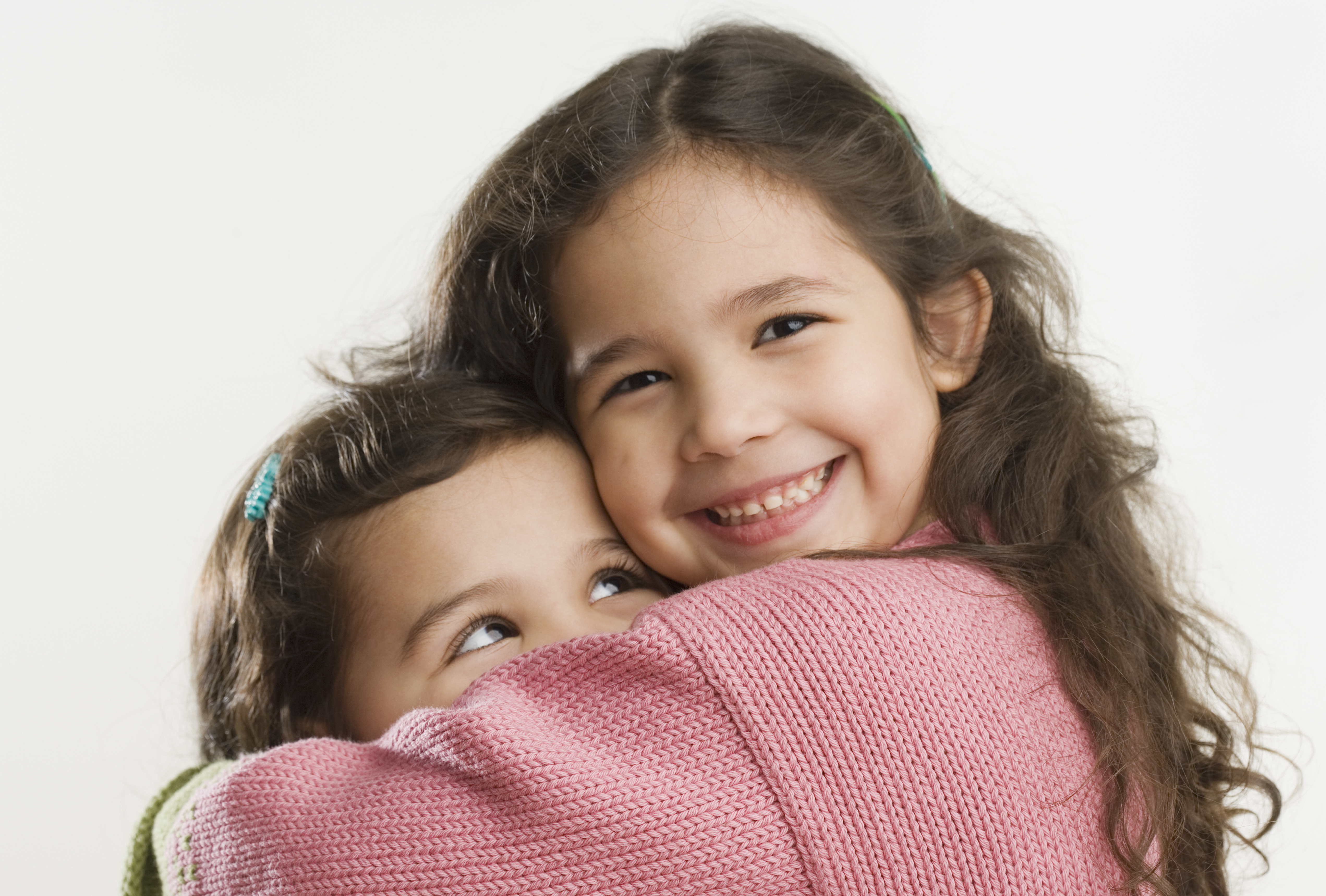 Studio shot of young Hispanic sisters hugging