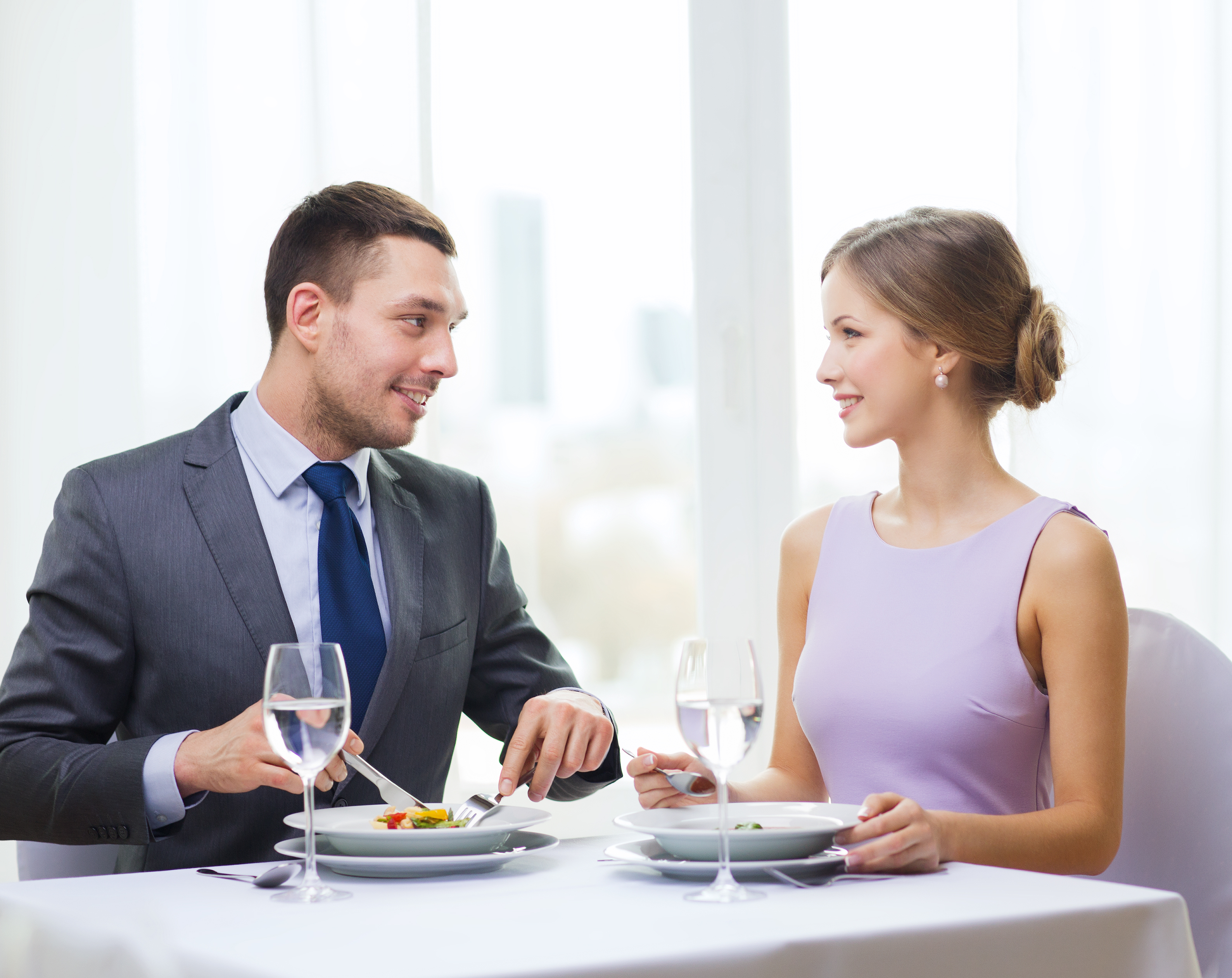 restaurant, couple and holiday concept - smiling couple eating appetizers at restaurant